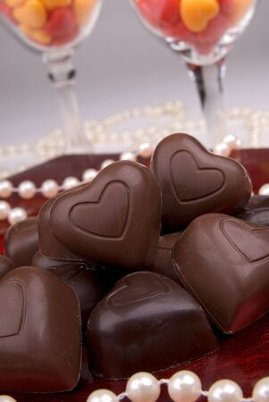 Chocolate heart candy on a red plate with pearls and wine glasses Banco de Imagens
