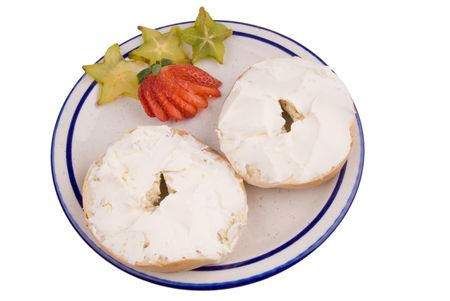garish: Bagel with cream cheese on a plate with strawberry and star fruit garish.