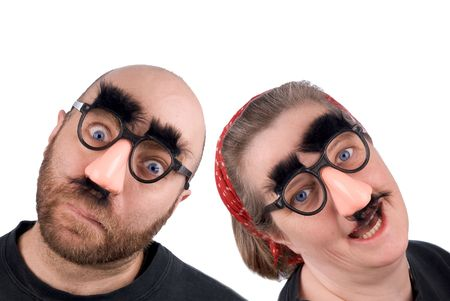 Couple wearing fake nose and glasses with mustashe and eyebrows over awhite background