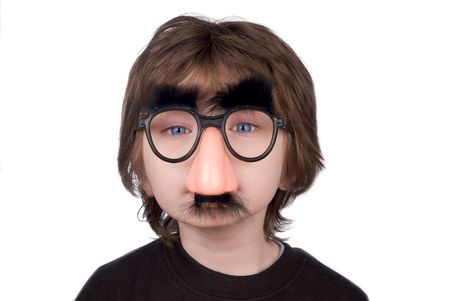 trickster: Boy wearing fake nose and glasses with mustashe and eyebrows over awhite background Stock Photo