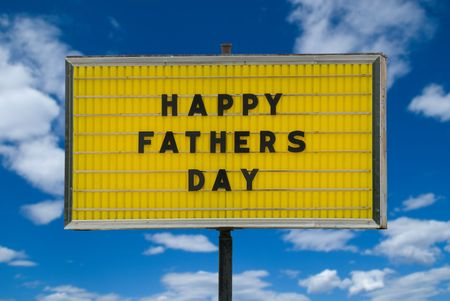 Happy Fathers day message on a yellow sign isolated on a cloudy sky background.