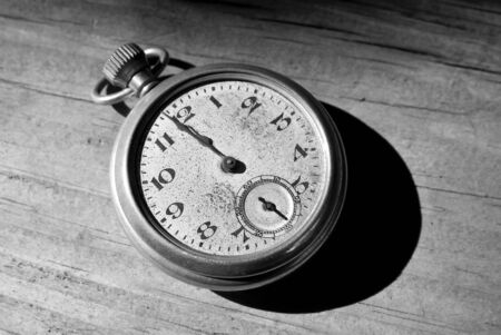 Antique pocket watch clock in black and white tone on a wood floor