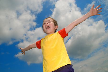 arms wide open: Boy with his arms wide open in front of a sky with clouds