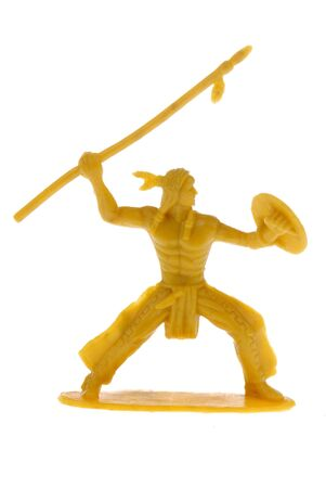 plains indian: yellow plastic toy American Indian warrior throwing a spear isolated over white