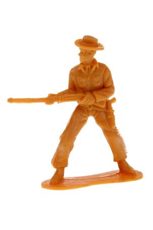plains indian: yellow plastic toy cowboy shooting a rifle from his hip isolated over white