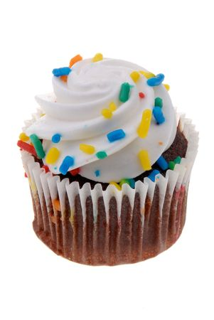 hundreds and thousands: Cupcake with white icing and colored sprinkles in wrapper isolated over white Stock Photo
