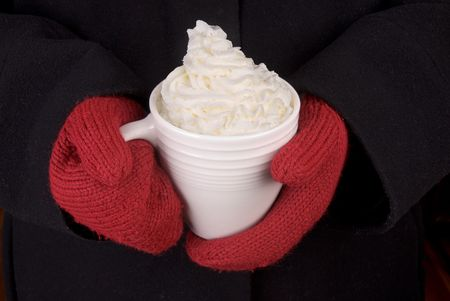 woman in a black coat with red mittens holds a Mug of Hot Chocolate with whipped cream