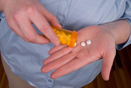 self dependent: Woman taking pills from a prescription bottle