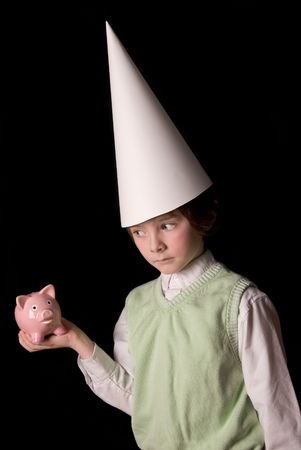 dunce cap: Sad young boy in a dunce cap with a piggybank over a black background