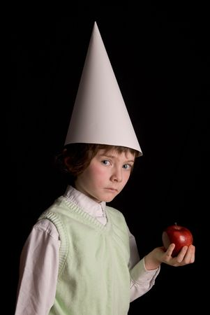 dunce cap: Sad young boy in a dunce cap with a red apple over a black background Stock Photo