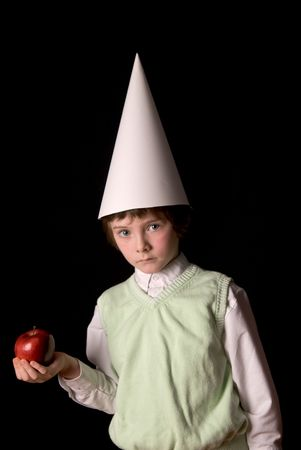 Sad young boy in a dunce cap with a red apple over a black background Reklamní fotografie