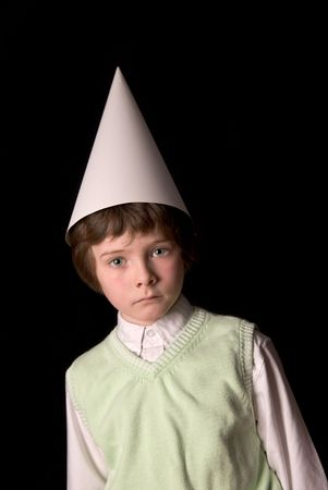 dunce cap: Sad young boy in a dunce cap over a black background