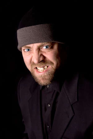 aggresive: Angry Man wearing a knit hat over a black background