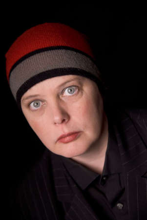 Woman wearing a knit hat over a black background Фото со стока