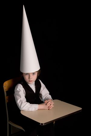 Sad young boy in a dunce cap at his school desk over a black background