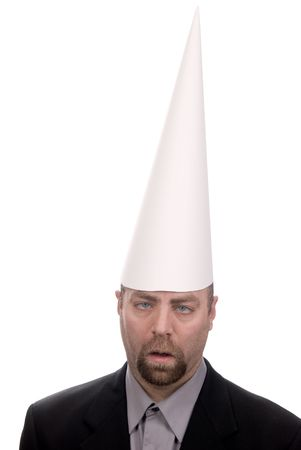 Man in a dunce cap with eyes crossed over a white background Stock Photo