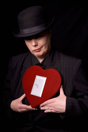 Woman in a derby and suit holding a red candy heart box with a light switch photo