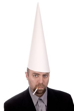 dunce cap: Man in a dunce cap smoking a cigarette over a white background