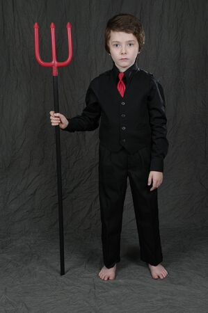 horrify: Young boy as a devil with  a trident isolated over gray Stock Photo