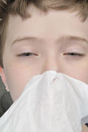 Young boy with a tissue having a cold close up photo