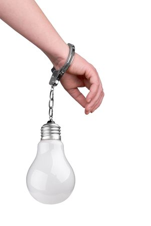 One hand handcuffed to a incandescent lightbulb isolated over white photo