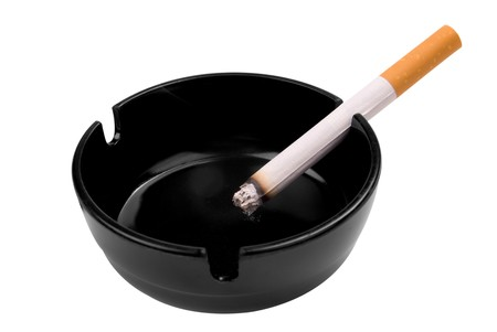 ashtray: Cigarette in a black ashtray isolated over a white background