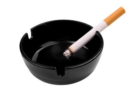 Zigarette in eine schwarze Aschenbecher über einen weißen Hintergrund isoliert