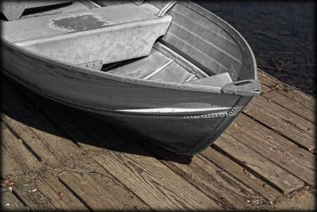 Metal old-fashioned row-boat sitting on the dock waiting for use