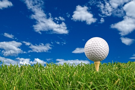 Golf ball close-up from the ground level with grass and cloudy sky