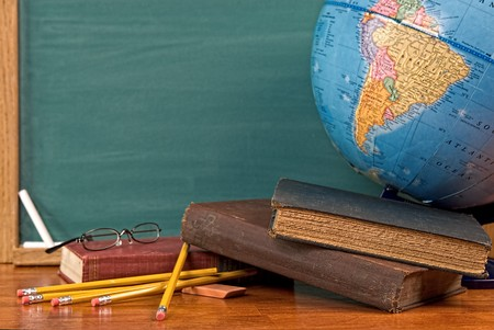 Old school books on a desk with a globe in front of a green chalkboard
