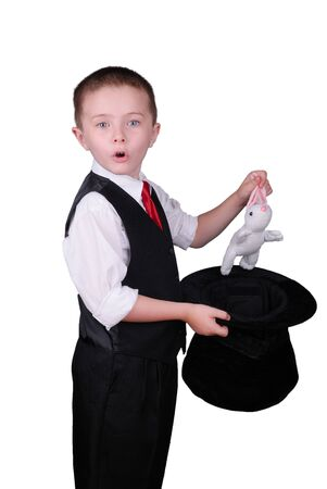 Child dressed as a magician pulling a rabbit from his hat isolated over a white background photo