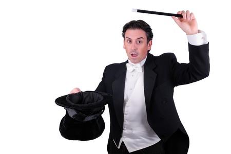mago: hombre vestido como un mago tirando de un conejo de su sombrero aislado sobre un fondo blanco
