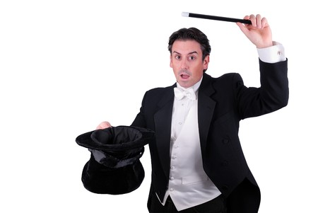man dressed as a magician pulling a rabbit from his hat isolated over a white background