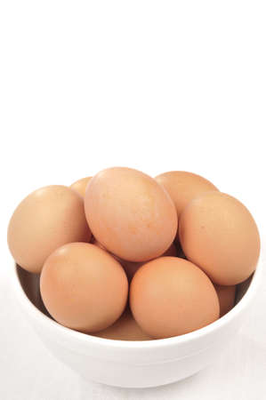 Brown Eggs in a white bowl isolated over a white background