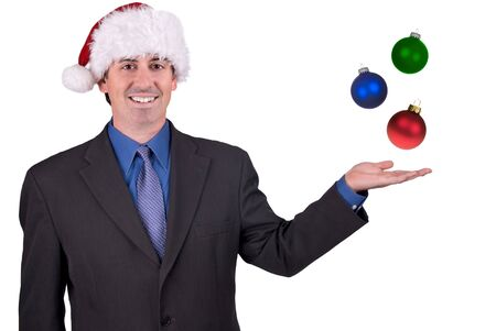 Businessman with a Christmas hat on his head with ornaments in his hand isolated over white Reklamní fotografie