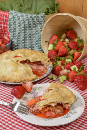 Strawberry-Rhubarb Pie on plate on a country table with strawberries and rhubard and a red and white checkered table cloth Reklamní fotografie