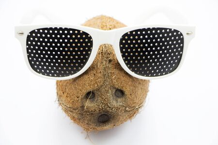 poor eyesight: Coconut in glasses on a gray background Stock Photo