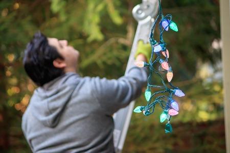 jonge man in grijs beklimmen van een ladder om te versieren voor Kerstmis Stockfoto