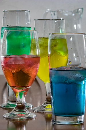 verticeal group of glasses with colorful water