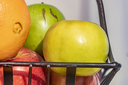 apples and an orange in a wire basket Stock Photo