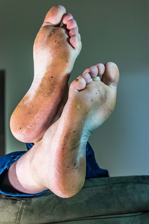 vertical feet dirty sole on crossed and relaxing on sofa