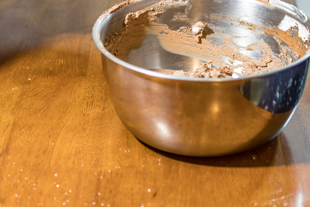 metal bowl with chocolate frosting