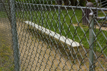 fence and bench at baseball field at park