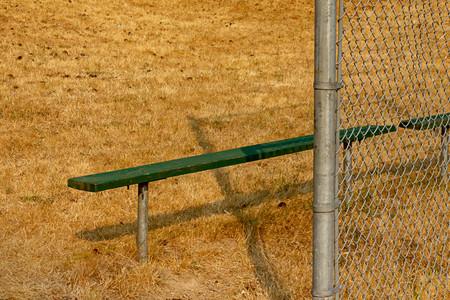 green bench on edge of summer ball field