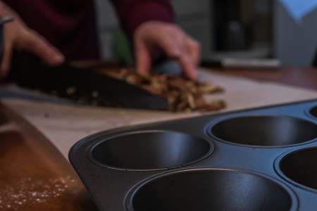 steel muffin tray on a table with pecans being chopped