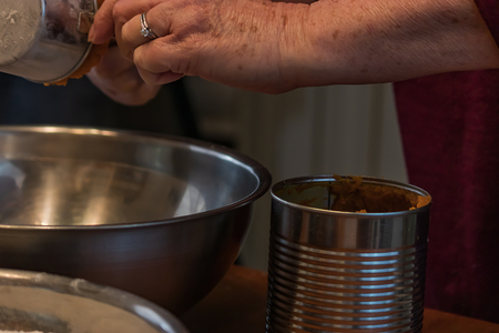pumpkin puree in a can being measured out into a silver bowl Banque d'images
