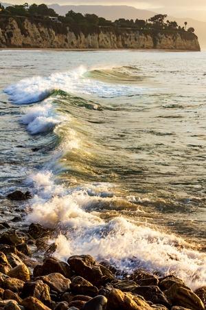 wave breaking on rocks at shoreline with sunrise