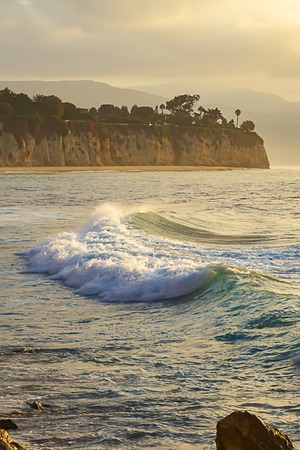 wave breaking at sunrise with peninsullla and cliff