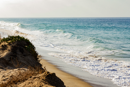 foaming fading wave on sandy shoreline, wave cresting, foaming backwash, sandy cliff rise