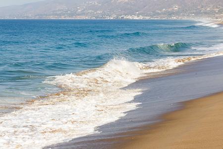 schäumende verblassende Welle an sandiger Küste, Wellenbergung, schäumende Rückspülung, Wellenbergung entlang der Küste, Standard-Bild